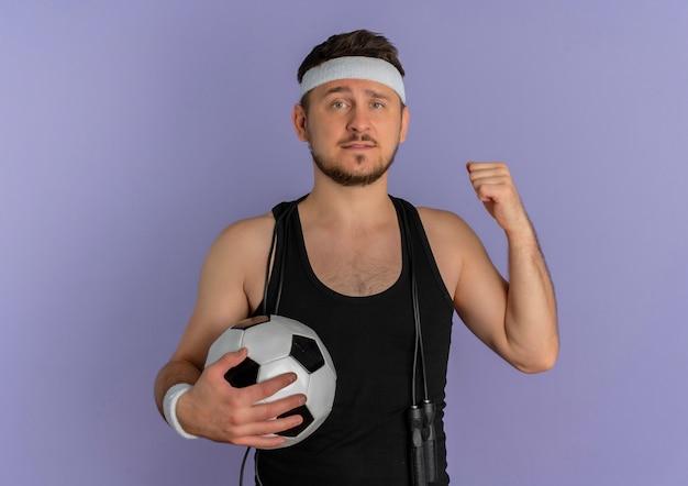 Junger fitness-mann mit dem stirnband, der fußball zeigt, der zurück schaut und zuversichtlich steht über lila wand