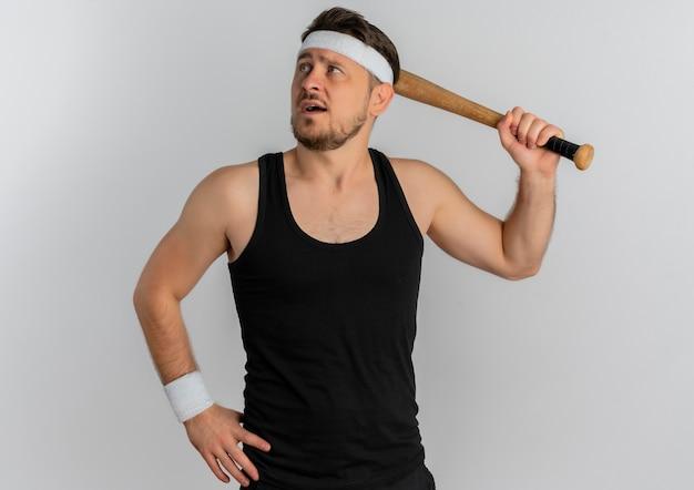 Junger fitness-mann mit stirnband, der baseballschläger hält, der mit dem sicheren ausdruck steht, der über weißem hintergrund steht