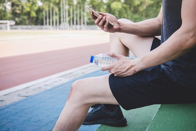 Junger fitness-sportler-mann, der auf bank mit flasche wasser sich vorbereitet, um auf straßenbahn zu laufen