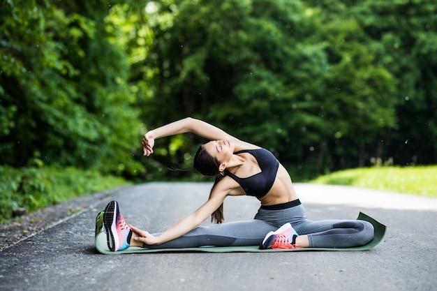 Junger fitnessfrauenläufer, der beine vor dem laufen im stadtpark streckt