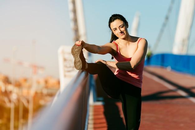 Junger fitnessfrauläufer, der die beine nach dem lauf ausdehnt