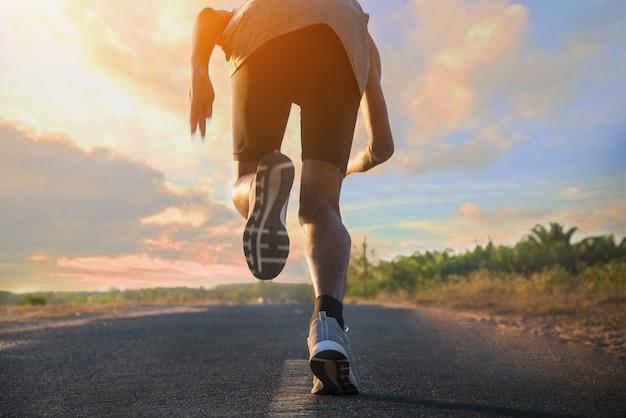 Junger fitnessmann, der an straße für übung läuft.