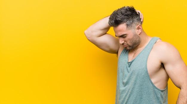 Junger fitnessmann, der hinterkopf berührt, denkt und eine wahl trifft