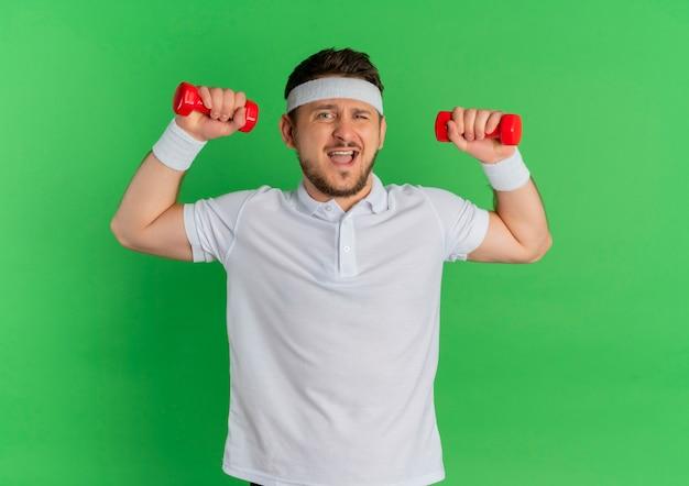 Junger fitnessmann im weißen hemd mit dem stirnband, das mit den hanteln arbeitet, die über grünem hintergrund stehen