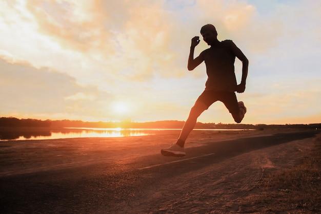 Junger fitnessmann-läufer-athlet, der an straße für übung läuft.