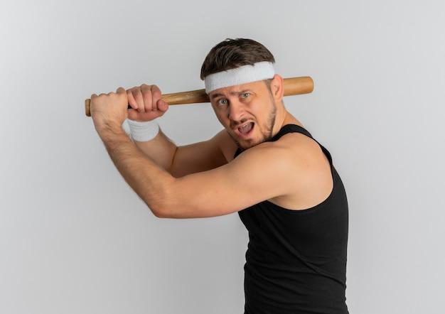 Junger fitnessmann mit stirnband, das einen baseballschläger emotional und aufgeregt schwingt, der über weißem hintergrund steht