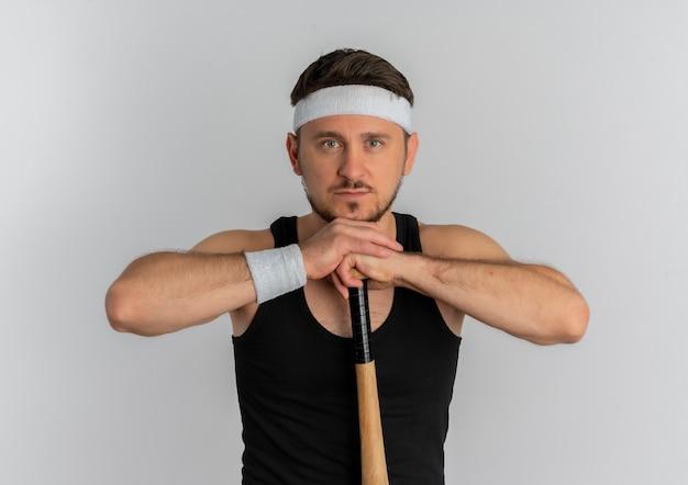 Junger fitnessmann mit stirnband, der baseballschläger hält kamera mit ernstem gesicht, das über weißem hintergrund steht
