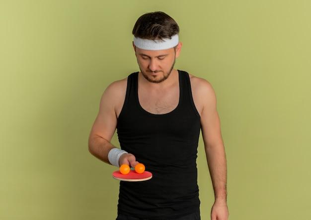 Junger fitnessmann mit stirnband, der schläger und bälle für tischtennis mit ernstem ausdruck auf gesicht steht, das über olivenhintergrund steht