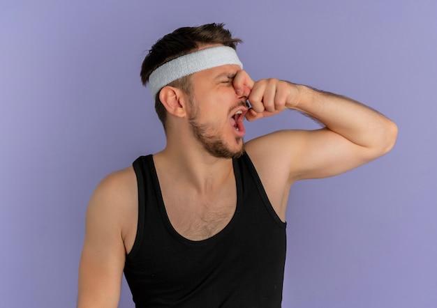 Junger fitnessmann mit stirnband, der seine nase mit den fingern schließt, die unter dem gestank leiden, der über lila wand steht