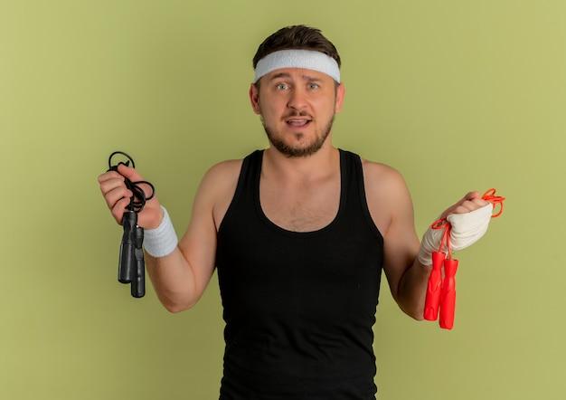 Junger fitnessmann mit stirnband, der zwei springseile hält, die verwirrt und unsicher schauen, die zweifel haben, die über olivenhintergrund stehen