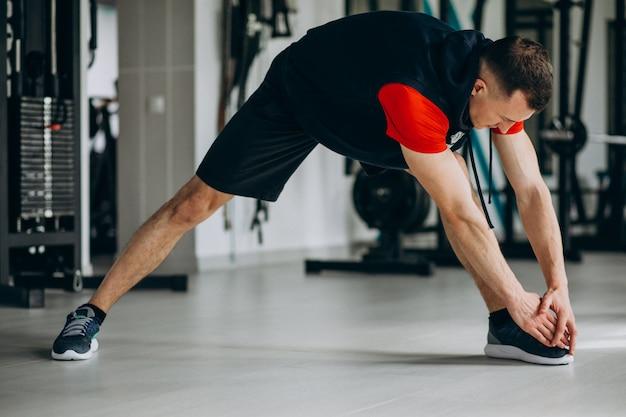 Junger fitnesstrainer, der im fitnessstudio streckt