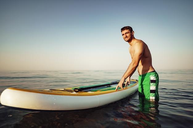 Junger fitter mann auf paddle-board, der bei sonnenaufgang auf dem see schwimmt