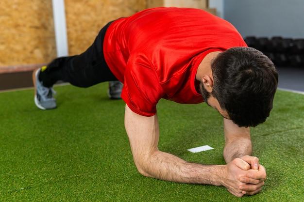Junger fitter mann, der in einem fitnessstudio trainiert