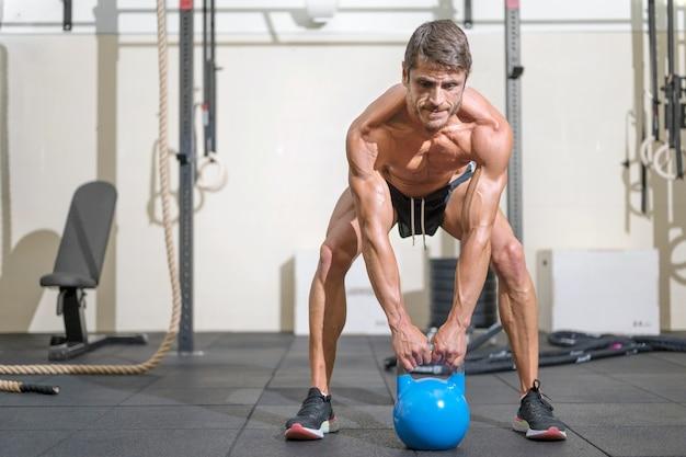 Junger fitter mann trainiert mit kettlebells