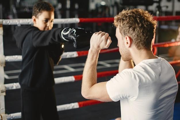 Junger fleißiger boxer, der das boxen lernt. kind im sportzentrum. kind, das ein neues hobby aufnimmt