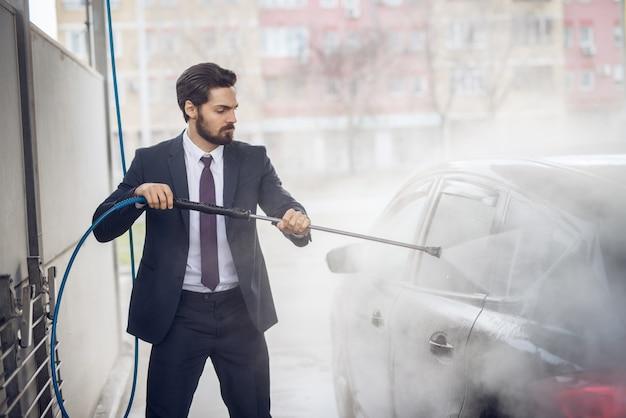 Junger fleißiger ernsthafter stilvoller bärtiger geschäftsmann im anzug, der das auto mit einer wasserpistole in der manuellen selbstbedienungswaschstation reinigt