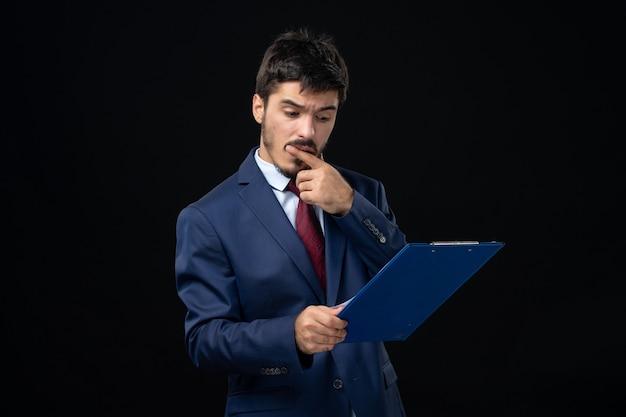 Junger fleißiger männlicher büroangestellter im anzug, der dokumente hält und statistiken an isolierter dunkler wand überprüft