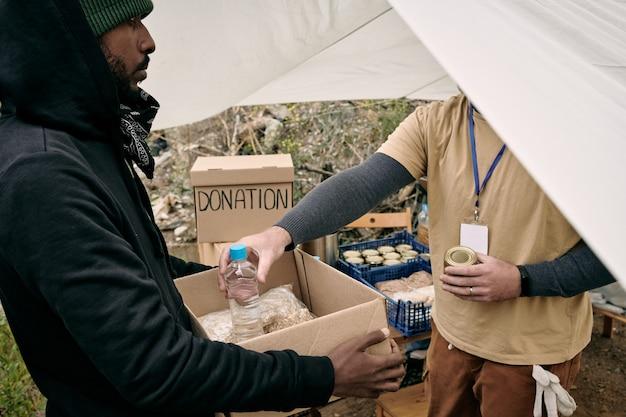 Junger flüchtling, der eine kiste hält, während er dort nahrung und wasser bereitstellt