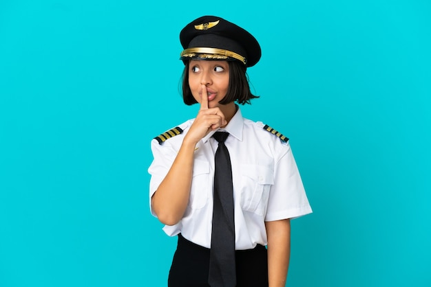 Junger flugzeugpilot über isoliertem blauem hintergrund, der ein zeichen der stille zeigt, geste, die finger in den mund steckt
