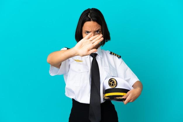 Junger flugzeugpilot über isoliertem blauem hintergrund, der mit der hand eine stoppgeste macht, um eine handlung zu stoppen