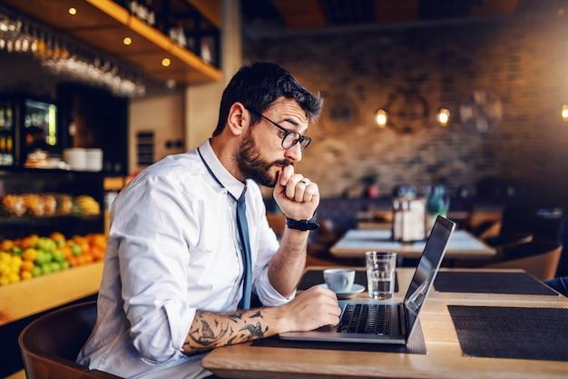 Junger fokussierter kaukasischer bärtiger geschäftsmann mit tätowierung und brille im hemd und in der krawatte, die im café sitzen und wichtige e-mail vom kunden lesen.