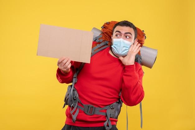 Junger fokussierter reisender, der eine medizinische maske mit rucksack trägt und ein blatt hält, ohne auf gelb zu schreiben