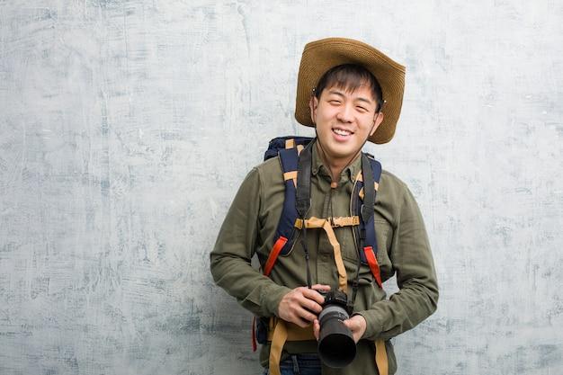 Junger forschermann, der eine kamera nett mit einem großen lächeln hält