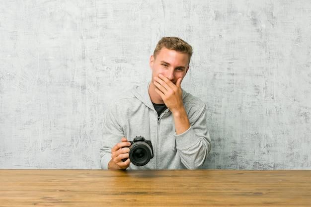 Junger fotograf, der auf einem tisch eine kamera lacht über etwas, mund mit den händen bedeckend hält.