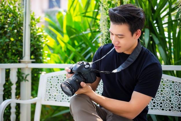 Junger fotograf, der bild nach genommenem foto überprüft