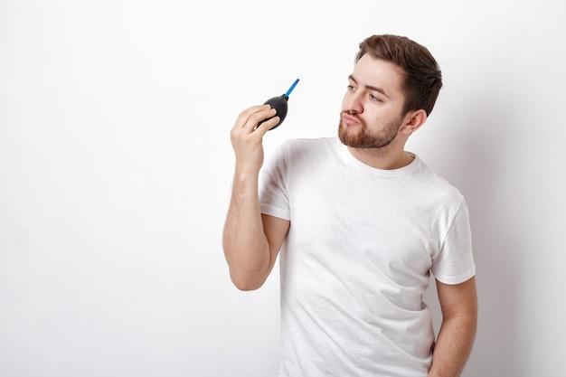 Junger fotograf, der die vakuumpumpe der kamerareinigung hält. gummi-luftgebläsepumpe staubreiniger für kamera und objektive. sanftes licht