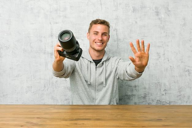 Junger fotograf, der eine kamera auf einer tabelle zeigt nr. zehn mit den händen hält.