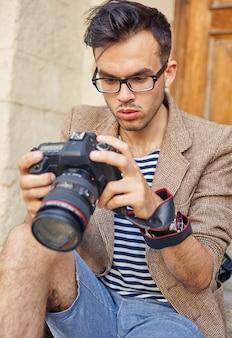 Junger fotograf, der fotos auf der kamera betrachtet