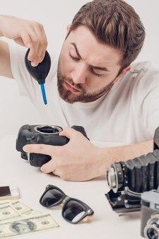 Junger fotograf, der kamera mit vakuumpumpe säubert. handbläser staubreiniger für kamera und objektive. sanftes licht