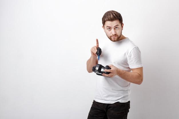 Junger fotograf, der kamera mit vakuumpumpe säubert. handbläser staubreiniger für kamera und objektive.