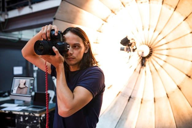 Junger fotograf, der vor einem reflektierenden regenschirm steht