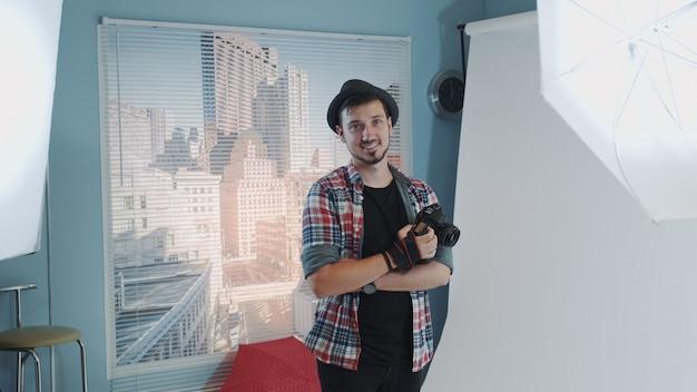 Junger fotograf im hut, der kamera hält und im modernen studio-fotoshooting lächelt
