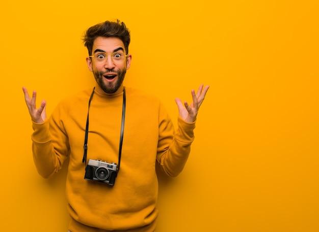 Junger fotograf mann, der einen sieg oder erfolg feiert