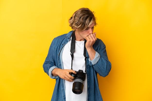 Junger fotograf mann isoliert auf gelb mit zweifeln