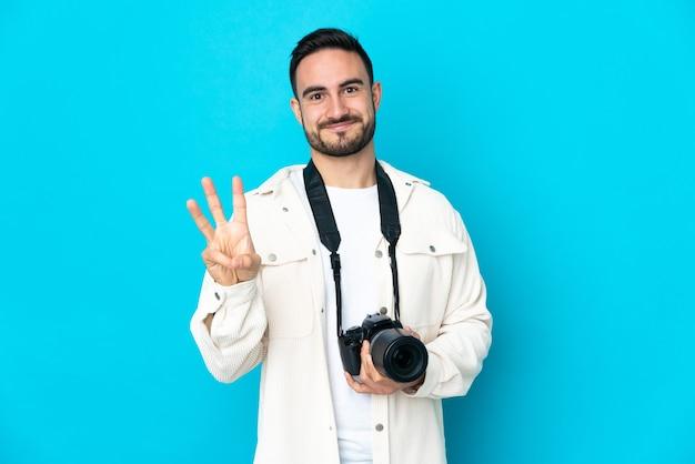 Junger fotograf mann lokalisiert auf blauem hintergrund glücklich und zählt drei mit den fingern