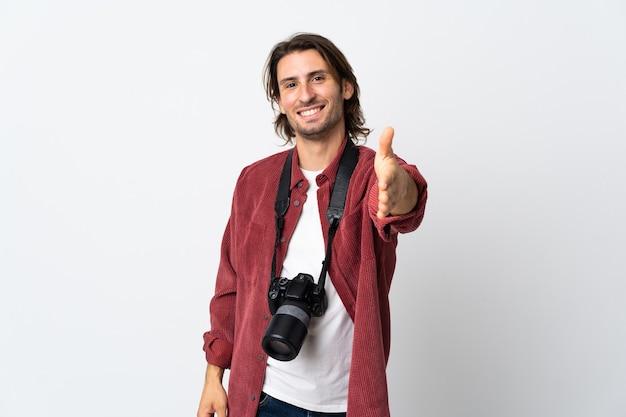Junger fotograf mann lokalisiert auf weißem hintergrund händeschütteln für das schließen eines guten geschäfts