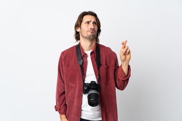 Junger fotograf mann lokalisiert auf weißem hintergrund mit den fingern, die kreuzen und das beste wünschen