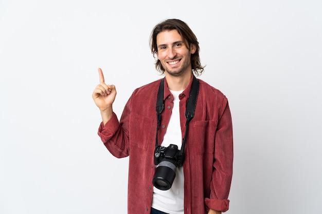 Junger fotograf mann lokalisiert auf weißem hintergrund zeigt und hebt einen finger im zeichen des besten