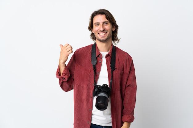 Junger fotograf mann lokalisiert auf weißer wand, die zur seite zeigt, um ein produkt zu präsentieren