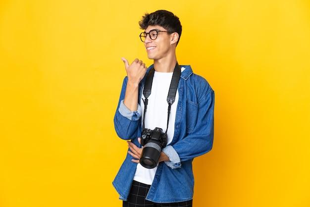 Junger fotograf mann über isolierte gelbe wand, die zur seite zeigt, um ein produkt zu präsentieren