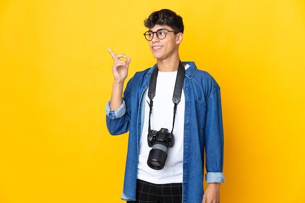 Junger fotograf mann über isoliertem gelbem hintergrund, der beabsichtigt, die lösung beim anheben eines fingers zu realisieren