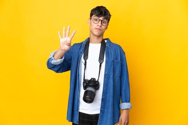 Junger fotograf mann über isolierten gelben glücklich und zählt vier mit den fingern