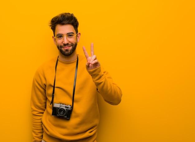 Junger fotograf mann zeigt nummer zwei
