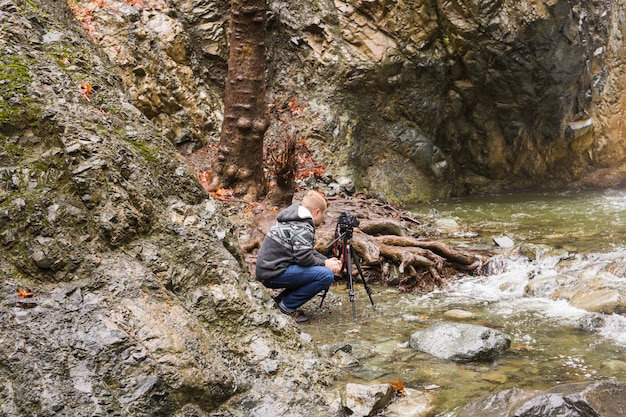 Junger fotograf mit rucksack, der fotos von wasserfall und felsen mit der kamera macht.