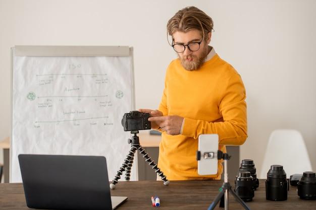 Junger fotograf oder fotografielehrer, der professionelle fotokamera während der online-lektion vor smartphone und laptop stellt