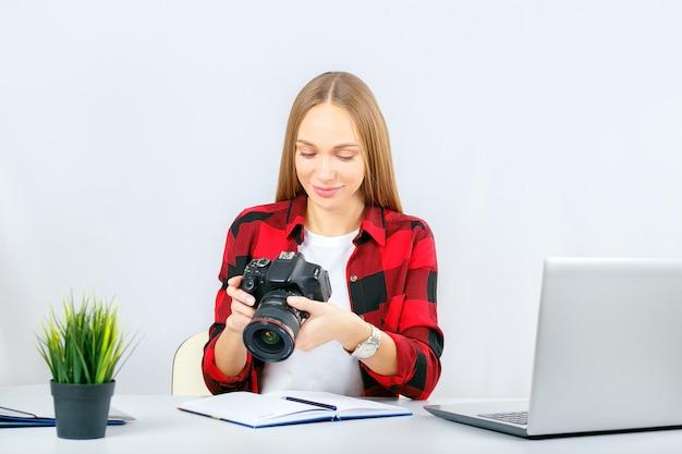 Junger fotograf oder grafikdesigner bei der arbeit im büro oder zu hause. frau im büro, das fotokamera betrachtet.